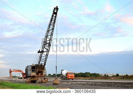 Large Crawler Crane Or Dragline Excavator With A Heavy Metal Wrecking Ball On A Steel Cable. Wreckin