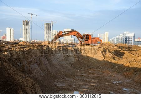 Excavator At Earthworks On Construction Site. Backhoe Loader Digs A Pit For The Construction Of The