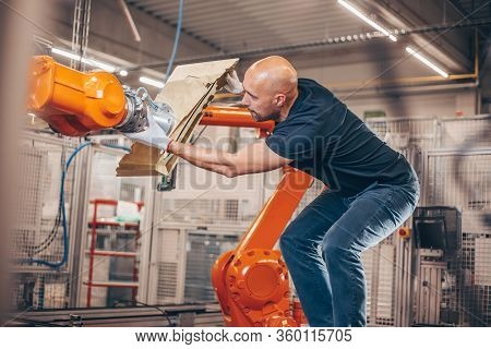 Engineer Setting Up Automatic Robot Arm For Production In Automotive, Industry Factory, Industrial C