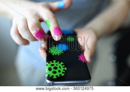 Close-up Of Persons Hand Holding Mobile Phone Covered With Microbe Stickers. Bacteria On Skin And Pe