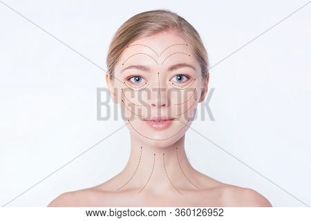 Portrait Of A Young Beautiful Woman With Drawn Massage Lines On Her Face. Skin Lifting Concept. Clos