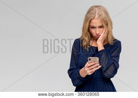 Portrait If A Shocked Young Girl In Dress Looking At Mobile Phone Isolated Over Gray Background