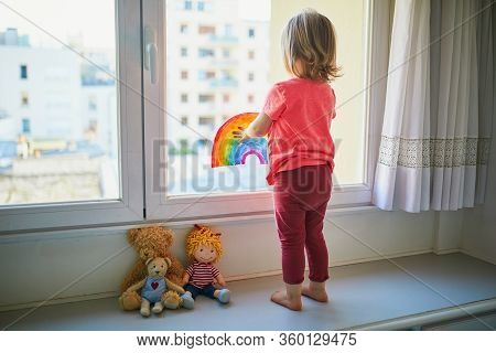Adorable Toddler Girl Attaching Rainbow Drawing To Window Glass As Sign Of Hope. Creative Games For