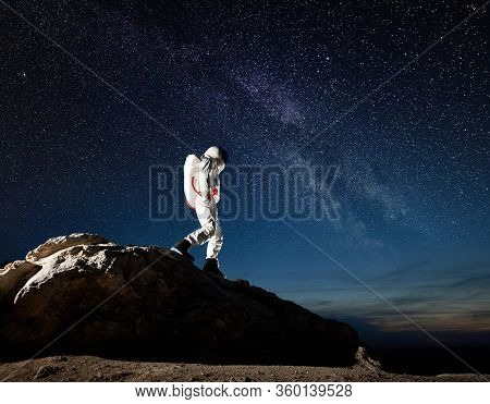 Astronaut Walking Down The Rocky Hill Under Fantastic Night Sky With Stars. Cosmonaut In Space Suit
