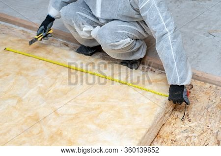 Cropped View Of One Workman In Overalls Working With Rockwool Insulation Material, Using Measuring T