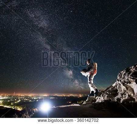Cosmonaut Standing On Rocky Hill Under Beautiful Night Sky With Stars And Milky Way. Space Traveler