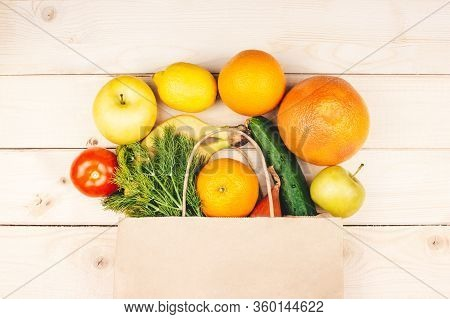 Paper Shopping Bag With Organic Vegetables And Fruits Flat Lay On Wooden Background Top View. Health