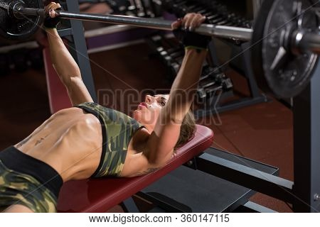 Sports Young Woman Doing Exercises With Barbell On Bench In The Gym. Bar Bench Press