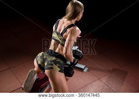Woman Bodybuilder In Gym Lifting Dumbbells On Bench.