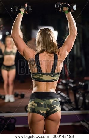 Beautiful Bodybuilder Woman With Lifting Dumbbells. Back And Hands Of A Young Sporty Muscular Woman.