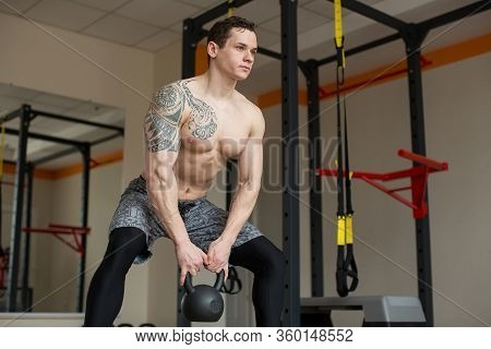 Beautiful Man Squats With Kettlebell At The Gym.