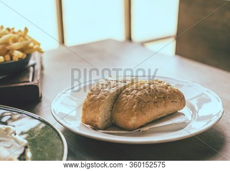 Ciabatta In White Plate. Ciabatta In White Plate On Wooden Table