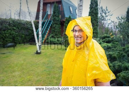 Portrait Of Beautiful Young Adult Caucasian Woman Under Bright Yellow Raincoat And Wellies Walking A