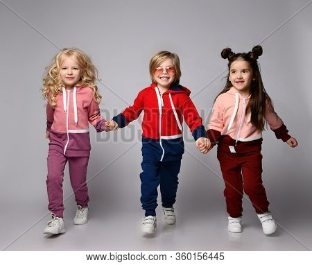 Full Growth Portrait Of Three Frolic Happy Smiling Kids Blonde And Brunette Girls And Blond Boy In M