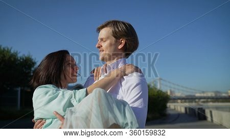 Handsome Young Guy With Brunette Girl In His Arms. Romantic Newlyweds Dance In The Park. A Guy Holds