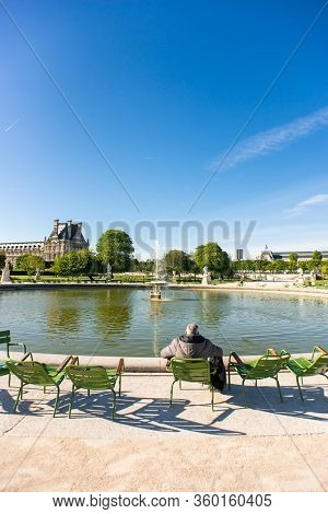 Paris. France - May 15, 2019: Lonely Man Sits and Relaxing on a Chair in Tuileries Garden.