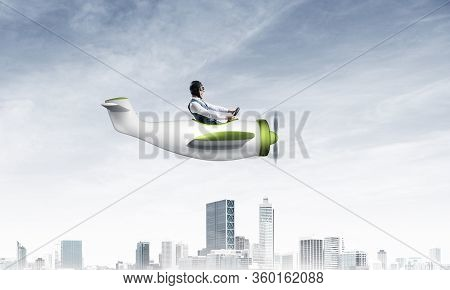 Businessman In Aviator Hat And Goggles Driving Propeller Plane Above Downtown With High Buildings. M
