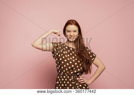 A Redhead Girl Is On The Pink Background. A Redhead Girl With The Biceps. A Strong Girl With Beautif