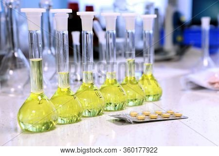 Conducting A Chemical Experiment In A Laboratory. Colored Flasks With Chemical Reagents. Many Glass