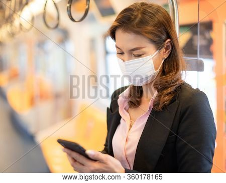 Bueatiful Adult Asian Businesswoman Passenger Wearing Medical Hygiene Protect Mask. Standing And Usi