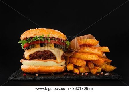 One Big Tall Classic Hamburger Burger Cheeseburger With French Fries On Black Stone Plate On Black B