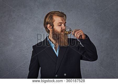 Handsome Bearded Well-dressed Man In Jacket Holding Glass Of Beverage Whiskey Alcohol Isolated Grey