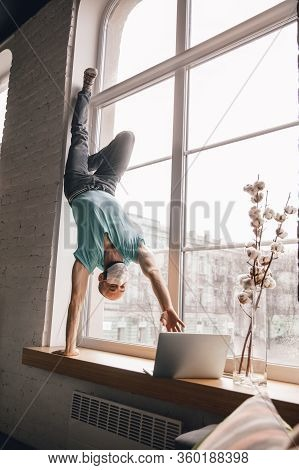Inspired. Young Man Doing Yoga At Home While Being Quarantine And Freelance Online Working. Remote O