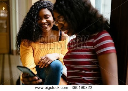 Two Girls Laughing Over Something Theyre Viewing On A Mobile Phone. Girl With Braids Laughing With H