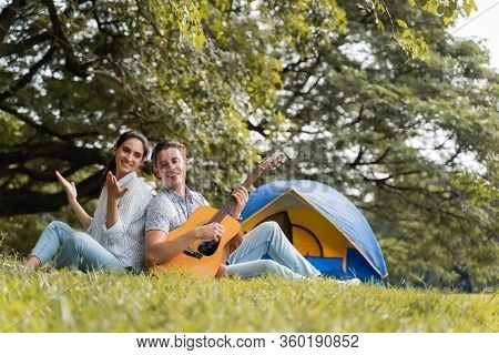 Picnic And Camping Time. Young Couple Having Fun With Guitar On Picnic And Camping In The Park. Love
