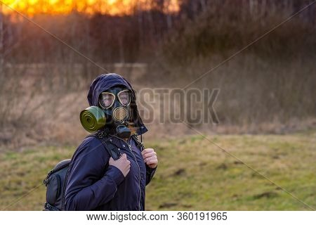 Covid-19. Girl In A Black Gas Mask And Dark Clothes With A Hood At Sunset On A Background Of Spring