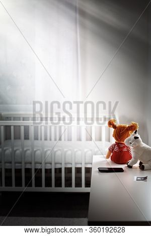 Childrens Gloomy Room With An Empty Cradle And Toys On The Dresser. Copy Space. Vertical. Concept Of