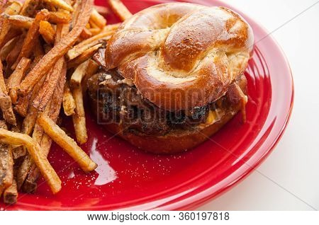 Gourmet Burger With Pretzel Bun And Fries On A Red Plate.  The Hamburger Has Gorgonzola Cheese, Baco