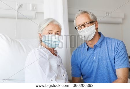 medicine, health safety and pandemic concept - happy senior man wearing face protective medical mask for protection from virus disease visiting his wife at hospital ward
