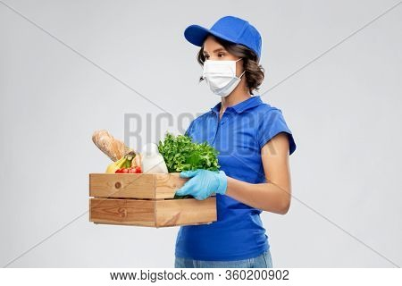health protection, safety and pandemic concept - delivery woman in face mask and gloves holding wooden box with food over grey background