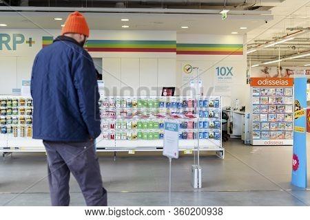 Faro, Portugal - Aprli 2, 2020: Man Waiting By Entrance To Radio Popular Shop Where Due To Coronavir