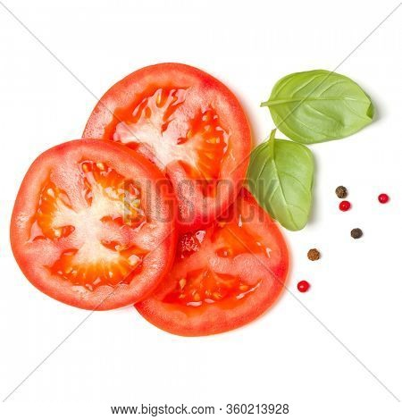 Slices of tomato and basil leaves isolated over white background. Top view, flat lay.