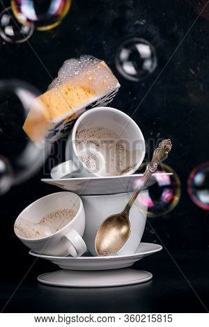 Washing Coffee Cups With A Washcloth With Foam, Conceptual Photo With Soap Bubbles