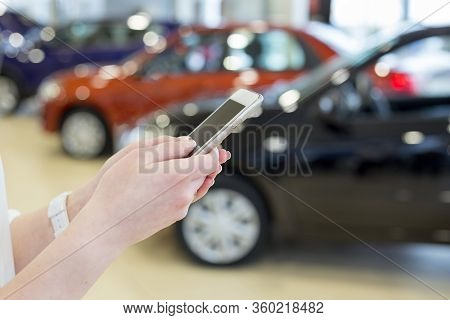 Woman Dealer Using Mobile Smart Phone At Dealer Showroom. Modern Working Process.