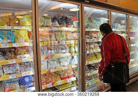 Kyiv / Ukraine. 09 March 2019: Man Choosing Food In Refrigerator Of Supermarket. Man Is Looking For
