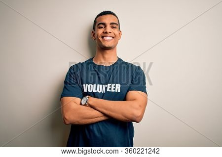 Young handsome african american man volunteering wearing t-shirt with volunteer message happy face smiling with crossed arms looking at the camera. Positive person.