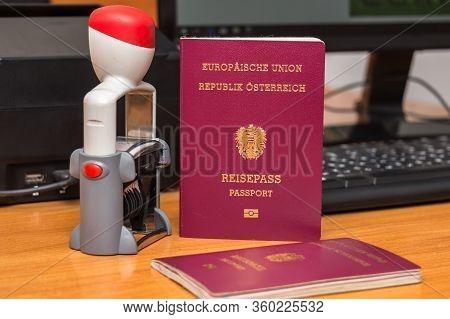 Close-up Of Austrian Biometric Passport With A Date Stamper, Interstate Border In Europe. Inscriptio