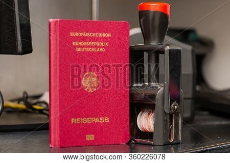 Red Biometric Passport Of A German Citizen With A Border Date Stamper, Close-up. Inscription - Europ