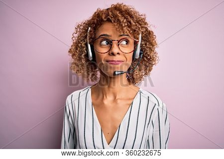 African american curly call center agent woman working using headset over pink background smiling looking to the side and staring away thinking.