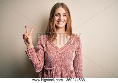Young beautiful redhead woman wearing pink casual sweater over isolated white background smiling looking to the camera showing fingers doing victory sign. Number two.