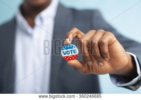 African Man Holding Vote Button On Blue Background For The November Elections In The United States 2
