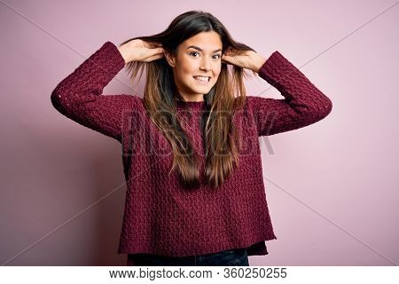 Young beautiful girl wearing casual sweater over isolated pink background Smiling pulling ears with fingers, funny gesture. Audition problem