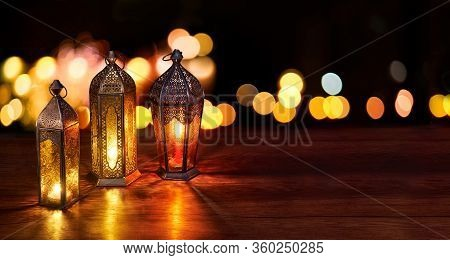 Ramadan Lanterns On The Table. Dark Background With Street Light And Bokehs. Beautiful Greeting Card