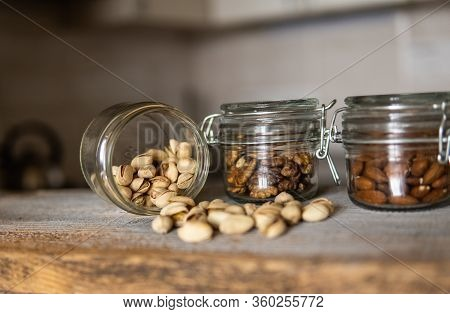 Pistachios Scattered On The White Vintage Table From A Jar And With Other Nuts On Background. Pistac