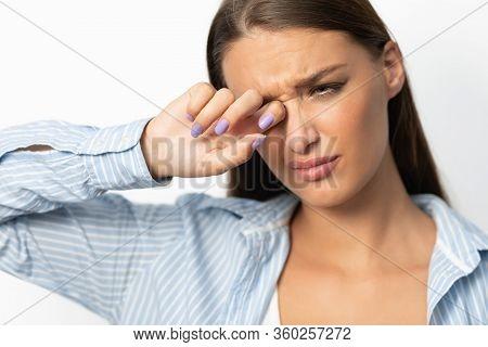 Coronavirus And Conjunctivitis. Woman Touching Aching Eye Having Covid-19 Symptoms Standing On White