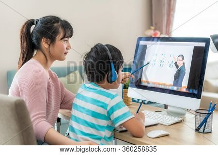 Asian Boy Student With Mother Video Conference E-learning With Teacher On Computer In Living Room At